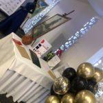 kiść-balonowa-balony-z-helem-złote-czarne-z-konfetti-przy-stole-z-nagrodami