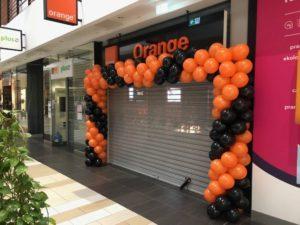 czarno pomaranczowa brama-z-balonow przed wejsciem do salonu w galerii handlowej