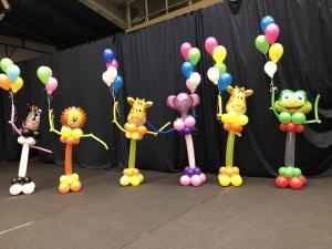 balonowe zoo - zwierzaki z balonów trzymające w jednej ręce kiść z balonów z helem